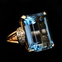 Aquamarine Ring accompanied by 36.00 carats. Also accompanied by Diamonds flanked on each side. Set in Yellow Gold.