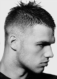 This haircut is commonly referred to as an aggressively tight taper. You will notice the hair is actually tapered shorter at the front hairline and a pointed element runs through the crown, creating a very contemporary shape.