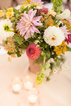Centerpieces of summer dahlias in terra cota pots. Photo by Anna J Photography