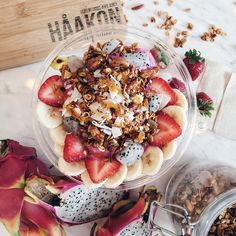 The PINK PITAYA. A healty frozen superfood bowl -- creamy blend of freshly made chia parfait and sweet chunks of pitaya. Topped with slices of passion fruit, strawberries, bananas, coconut flakes and house-blend granola. Finished with a quick drizzle of organic honey.