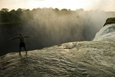 Looking over the edge of Victoria Falls from a swimming hole, Zambia, Annie Griffiths.