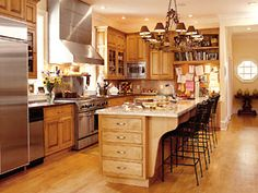 This kitchen includes a command center in the form of a built-in desk unit, placed in the heart of the space. A busy homeowner can make phone calls and catch up on correspondence while keeping an eye on this high-traffic area. Above the desk are two built-in bookshelves that house a collection of cookbooks, and the back of the desk is a bulletin board where important notes can be hung