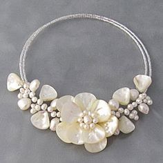 This beautiful choker features white freshwater pearls and shimmering white mother of pearl in a flower design. The necklace is handmade of memory wire by talented artisans in Thailand.