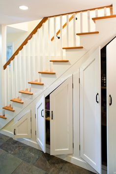 Cupboard under the stairs with concertina doors that open for Kitchen units under stairs