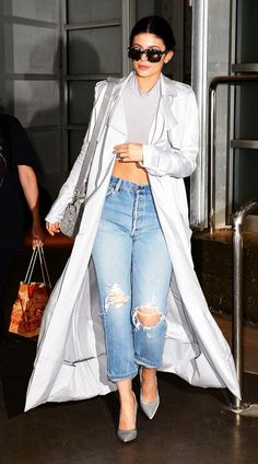 Kylie Jenner wears a silky duster over a gray crop top with distressed jeans and and statement pumps