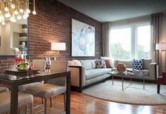 déco murale aspect brique rouge tout au long du mur qui crée une connexion optique entre le coin salon et le coin repas
