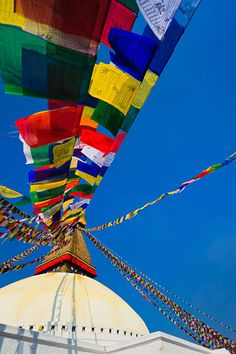 An ancient stupa surrounded by colourful prayer flags at the UNESCO World Heritage Site of Bodhnath, also called Boudha or Bouddhanath, one of the holiest Buddhist sites in Kathmandu.  Via, Coole Photography.