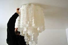 A faux capiz chandelier can cover an unsightly apartment light fixture!  And can be easily removed when you move!