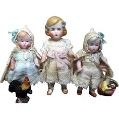 Set of three little all bisque dolls, the little ones with cotton outfits adorned with antique laces  a lacy hooded capes measure 3 1/2 with joined