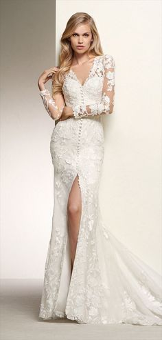 Pronovias 2018 Spectacular long-sleeve wedding dress in lace - Spectacular long-sleeve wedding dress in lace and thread embroidered flowers, with buttons from top to bottom and an invisible zip fastener. A form-fitting dress that streamlines curves and accentuates sensuality thanks to a V-neck, long sleeves with illusions and a tattoo back in crystal tulle. A very sensual and elegant dress that celebrates romanticism in every stitch.