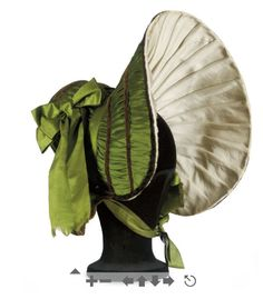 ornamentedbeing:    A GREEN SILK BONNET 1830S of extravagent shape, wide brimmed and lined in pleated cream silk, trimmed with chocolate velvet ribbons and later wide green silk ribbons