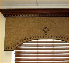 Window treatment- cornice with nail head trim and wood molding at top.