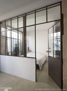 Une verrière au style industriel permet de séparer cette chambre minimaliste du reste de la maison.