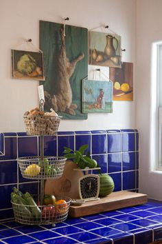 great cobalt kitchen tiles, plus- what a great way to hang a collection of paintings without framing.