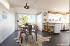 The open-plan dining room and kitchen are painted in Resene Black White and look over stunning views of the Waitakere Ranges.  http://www.habitatbyresene.co.nz/darren-and-staceys-tranquil-weatherboard