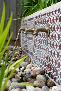Beautifully detailed Moroccan tiling from Habibi Interiors forms the backdrop to this simple water feature. We had this bespoke panel made from the clients choice, fitted by Earth Designs www.habibi-interi... #moroccantiles #moroccangarden #waterfeature #pebbles