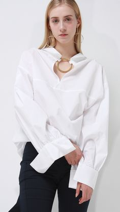 Lemaire crisp classic shirt in white. It has one pocket at front and gold circular ring at back with deep V-neck collar. Extra long sleeves and ruched cuffs. Worn with Gwynn Ruffle Pants care instruct