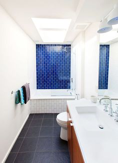 Vertical subway, feature wall of color, warm wood floating vanity with white counter & integrated sink