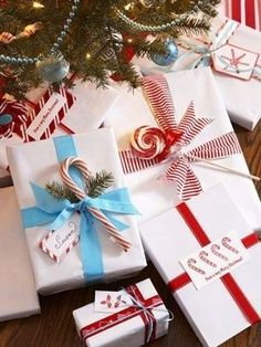 Christmas wrapping idea: white paper for all packages with different color ribbon for each child