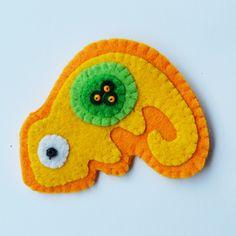 Chameleon+-+menší+Brož+ve+tvaru+chameleona,+ušitá+z+pevného+a+tlustého+filcu.+Je+pošitá+korálky.+Hodí+se+na+jakékoli+oblečení+-+tričko,+sukně,+kabátek+-+i+na+tašku,+nebo+jen+jako+ozdoba+na+záclonu.+Zezadu+je+přišitá+brožová+spona.+Rozměry+jsou+7+x+6+cm.
