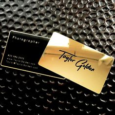 Gold and black metal business cards with a polished gold finish.