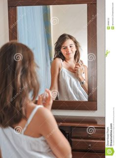 A Beautiful Teen Girl Studies Her Appearance As She Looks Into The ...