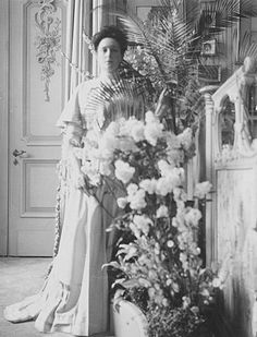 Alexandra standing in the Mauve Room outside the door to the Pallisander Room. To her left was a large arched greenhouse-like window which provided sunlight for the plants kept alongside a Louis XVI style screen. This lemonwood carved screen was set with crystal and lined with violet colored silk. It partioned off the location of her famous mauve chaise.