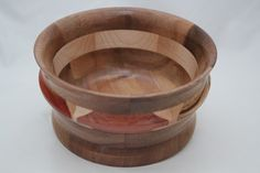 The Exotic Woods Bowl has 19 pcs of exotic woods: Bubinga (Africa) light red with dark streaks, Padauk (Africa) red-orange with dark streaks; Monkey Pod (C&S America) tan with streaks, Zebrawood (West Africa) creamy tan with dark streaks, domestic woods: Walnut (USA) med. brown (1 pc), White Maple (USA) light tan (6pcs). It has a multi-layer hand applied acrylic finish. # 638  0750