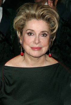 Catherine Deneuve looks fabulous in her orange drop earings, boatneck black blouse and those big kohl-lined eyes. Inspiration for us all.
