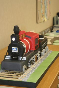 "Thanks to the North Carolina Railroad Company for the opportunity to make such a cake for such a special occasion. 38"" Train Cake, Vanilla White Cake, Milk Chocolate Ganache, Complete with Working Headlight. Railroad ties made from woodgrained marbled fondant. Chopped up fondant for gravel!"