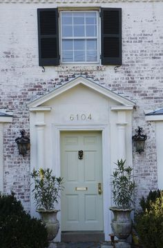 Pale aqua shutters on an off white brick house with white Very light mint green paint