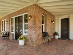 A wide brick porch is shaded from the sun by a beamed ceiling. All-weather furniture, exterior lighting and potted plants combine to create an outdoor space that's both traditional and comfortable.
