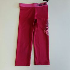 """Nike Pro Capri This lovely pair of nike dri fit pro capri are brand new with tags still attached. They are a lovely dark frushia pink and the waist band is a lighter pink. The left leg instead of a swoosh has Nike wrote out with snake animal skin design. These are a size xsmall and the inseam is 18"""" long. Great for the gym, cheer, yoga, lifting, running and so much more. Nike Pants Capris"""