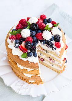 Eton Mess Cake with layers of sponge cake, sweetened whipped cream, crispy meringues, and fresh berries.