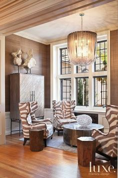 Luxe Brown and white living area with graphic patterned chairs and contemporary furnishings & Stunning Chandelier <3