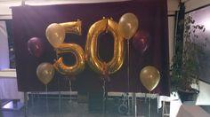 Photocall 50 años con fondo terciopelo granate, globos dorados del nº 50  y globos granates y dorados a los lados.