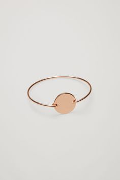 Made from shiny metal, this bangle is designed with a circle disc detail that is also the bracelets fastening.