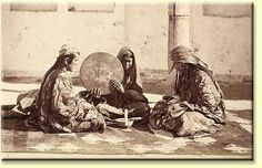 A n interesitng photo depicting three women seated, partaking in what has been called wedding cermonies. But of note is their dress, as well as the interesiting flat woven textile on which they are seated.