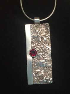 One-of-a-kind Reticulated sterling silver pendent with 10mm round garnet size…