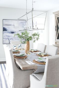 Dining room table setting for spring with navy blue, white and wood tones. Beautiful oversized blue abstract art!