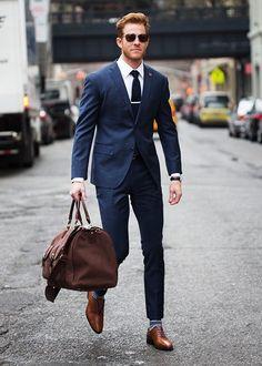 Den Look kaufen: https://lookastic.de/herrenmode/wie-kombinieren/anzug-businesshemd-oxford-schuhe/16378   — Weißes Businesshemd  — Schwarze Krawatte  — Dunkelblauer Anzug  — Schwarze Lederuhr  — Braune Segeltuch Reisetasche  — Dunkelblaue horizontal gestreifte Socke  — Braune Leder Oxford Schuhe