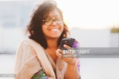 Stock Photo : young woman using smart phone in the sun
