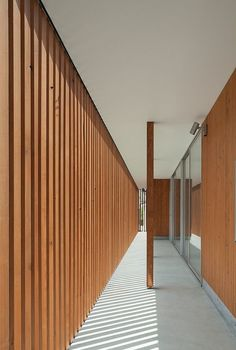 contemporary transitional space / exterior passage enclosed with vertical louvers/wood screen for privacy
