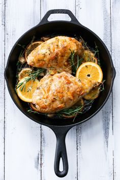 Skillet roasted bone-in chicken breasts on a bed of oranges, garlic and herbs, slathered with a tangy orange marmalade glaze