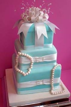 Tiffany Blue and white three tier wedding cake decorated with strands of pearls, white satin ribbons