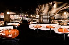 STK at The Cosmopolitan in Las Vegas has dark  booths, white leather benches, circular wooden tables, exposed columns, hanging light fixtures, and unique sculptures.
