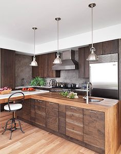 waterfall woodtop + walnut cabinetry + metal pendants + plaster backsplash