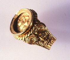 Romano-British. Gold ring with filigree, 'basket' pattern, and clasped hands on bezel. The hoop is a thin band of gold sheet, undulating and impressed to resemble basket-work. It is bordered on each side with beaded wire. The shoulders have neat, elaborate spirals in gold wire on a thin backing sheet. Surrounding the oval bezel is a roped flange, and within the setting is a gold plaque decorated in repoussé with a pair of clasped right hands (dextrarum iunctio) within a beaded border.