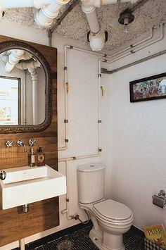Os canos ficam expostos no lavabo da casa com estilo loft habitada pelo casal Viviana Ximenes e GG Mattar. O painel de madeira com espelho quebra um pouco o clima industrial