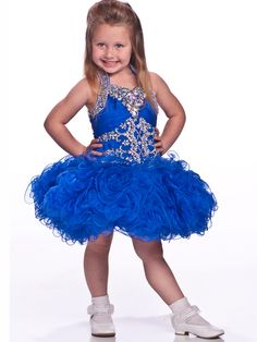 Your little girl will over shine the rest of the contestants when performing in this adorable short pageant dress by Unique Fashion UF1090. Beaded halter straps secure a v-neckline bodice which is amazingly embellished with colorful rhinestones as well as beadwork and has an asymmetrical ruched band with center cluster. A dropped waist opens way to a graceful all over ruffled skirt. Order today in Neon Pink, Purple, Royal, Tangerine or White. PageantDesigns.com has the right accessories to…